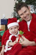 Portrait Of Father And Son In Santa Claus Outfit Holding Present - stock photo