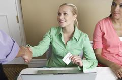 Receptionist Distributing Name Tags - stock photo