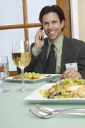 Businessman On A Call At Dining Table - stock photo
