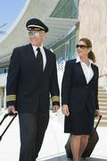 Pilot And Flight Attendant Outside Building - stock photo