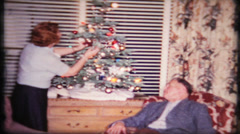 Housewife decorates Christmas tree at home, 45 vintage film home movie Stock Footage