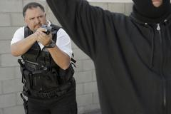 Police Officer Aiming Gun At Thief Stock Photos