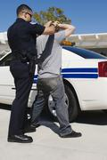 Officer Arresting Young Man - stock photo
