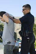 Police Officer Arresting Young Man Stock Photos