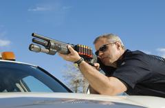Police Officer Aiming Shotgun - stock photo