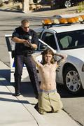 Police Officer Arresting Young Man - stock photo