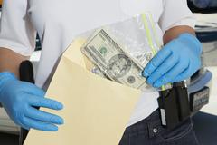 Police Officer Putting Money In Evidence Envelope - stock photo