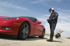 Traffic Cop Talking With Driver Of Sports Car - stock photo