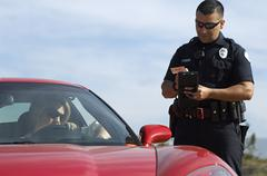 Traffic Cop By Sports Car - stock photo