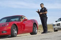 Traffic Cop Standing By Sports Car - stock photo