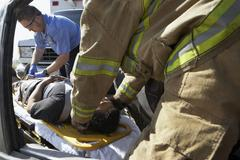 Firefighter And Paramedics Helping Car Crash Victim - stock photo