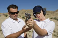Instructor Assisting Woman With Hand Gun Stock Photos