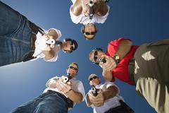 Group Of people In Circle Aiming Guns - stock photo