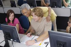Senior Teacher Assisting Students - stock photo