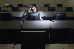Female Student Scratching Head While Looking At Computer Stock Photos