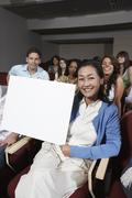 Teacher Holding Billboard With Students In The Background Stock Photos