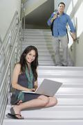 Female Student Sitting While Man Walking Down Stairs - stock photo
