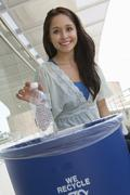 Female Student Throwing Plastic Bottle In Dustbin - stock photo