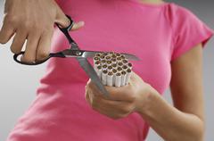 Woman Cutting Bundle Of Cigarettes - stock photo
