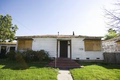 Abandoned House With Boarded Up Windows - stock photo