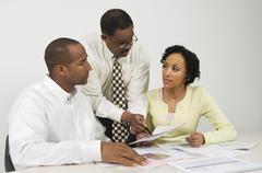 Advisor Explaining Financial Plans To Couple - stock photo