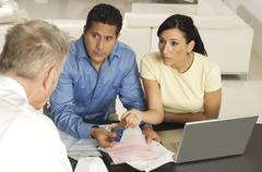 Couple Giving Documents And Credit Cards To Advisor - stock photo