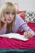 Girl Writing On Book In Bed - stock photo