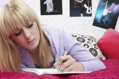 Female Student Writing In Book On Bed - stock photo