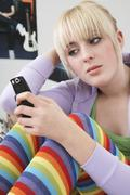 Girl Reading Text Message On Mobile Phone - stock photo