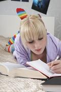 Student Writing In Book While Lying On Bed - stock photo