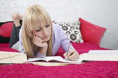 Teenage Student Writing In Book On Bed - stock photo
