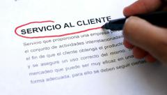 Stock Video Footage of Circling Customer Service with a pen (In Spanish)