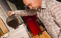 Production house owner weighing roasted coffee for packaging distribution Stock Photos
