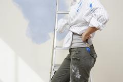 Woman Holding Paintbrush By Stepladder Against Unpainted Wall Stock Photos
