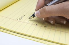 Hand Writing List Of Goals On Notepad - stock photo