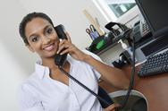 Stock Photo of Businesswoman Communicating On Landline Phone