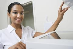 Businesswoman Using Fax Machine In Office Stock Photos