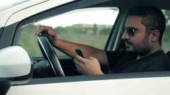 Irresponsible man behind the wheel and texting on his cell phone - stock footage