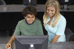Male Student And Teacher Using Computer Stock Photos