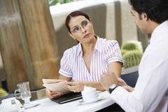 Stock Photo of Businesswoman Holding Newspaper While Looking At Colleague