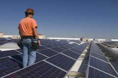 Stock Photo of Electrical Engineer Among Solar Panels