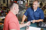 Stock Photo of Customer Making Payment In Motorcycle Shop