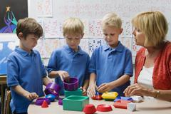 Teacher Helping Little Boys Assemble Educational Puzzle Toys Stock Photos