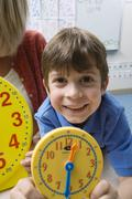 Boy Showing Yellow Clock With Teacher In Background Stock Photos