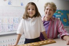 Teacher And Schoolgirl With Counting Tray Stock Photos