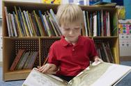 Stock Photo of Boy Reading Picture Book