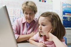 Teacher Helping Schoolgirl Use Laptop - stock photo