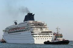 cruise ship leaves the port city with the help of powerful naval tugs - stock photo
