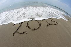 waves of the sea on the beach that erase the year 2013 - stock photo