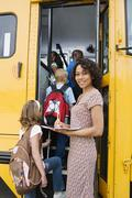 Teacher Loading Elementary Students On School Bus Stock Photos